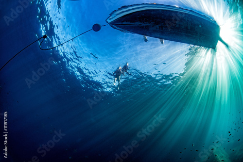 Photo boat ship from underwater blue ocean with sun rays