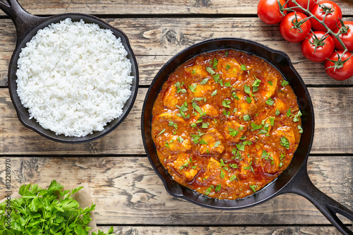 Traditional tikka masala chicken spicy meat Indian food with rice tomatoes and parsley in cast iron skillet on vintage wooden background
