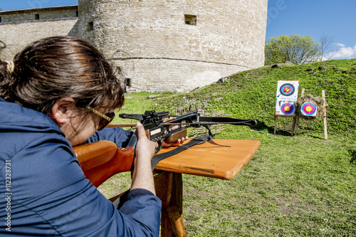 Fotografia Girl shoots a crossbow from the walls of the fortress in Staraya