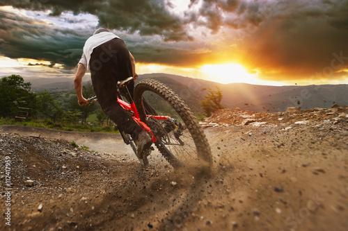 Człowiek na rowerze górskim jeździ na szlaku w burzliwy zachód słońca.