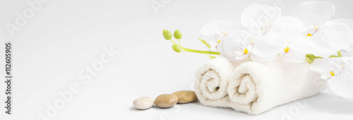 Spa orchid with soft towels and massage stones setting