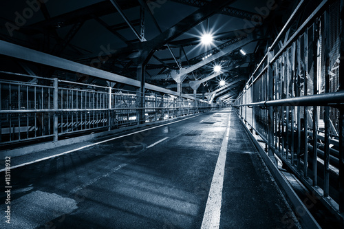 Moody monochrome view of Williamsburg bridge pedestrian walkway by night in New York City