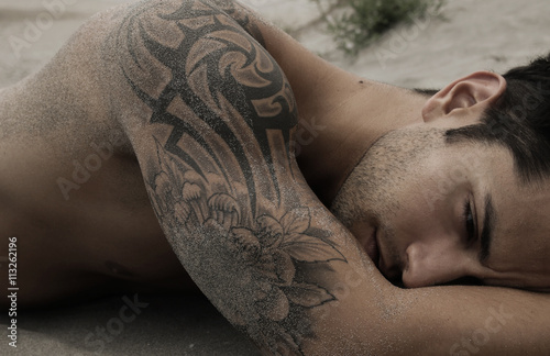 Wallpaper Mural Handsome male lying on the sand