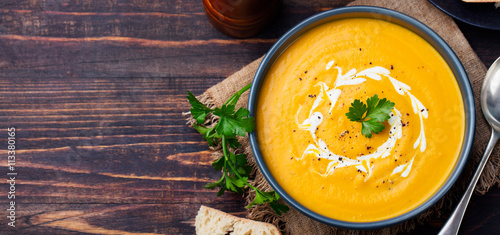 Canvas Print Pumpkin and carrot soup with cream and parsley on dark wooden background Top vie