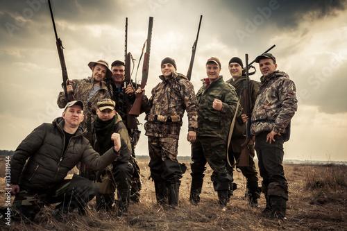 Fototapeta Hunters standing together against sunrise sky in rural field during hunting season