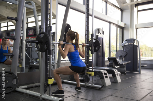 Rear View Of Young Woman Lifting Weights In Gym