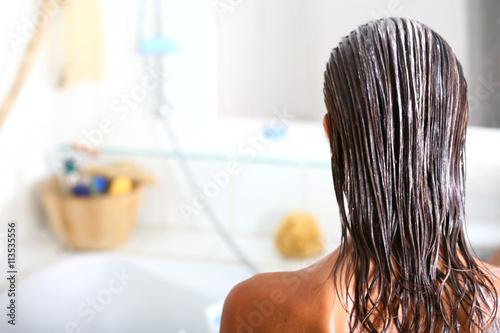 Slika na platnu femme dans sa salle de bain soignant ses cheveux