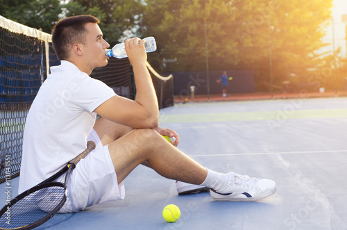 Canvas Print Young tennis player drinking water after playing, sitting on court and looking a