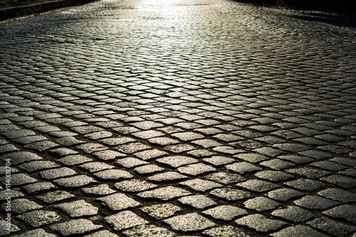 Cuadros en Lienzo sunlight on cobblestone road. old stone texture