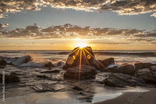 Obraz na płótnie Zmierzch słońca nad skałami przy plaży