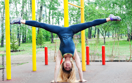 Obraz na plátně Beautiful young woman exercising outdoors workout on the bars