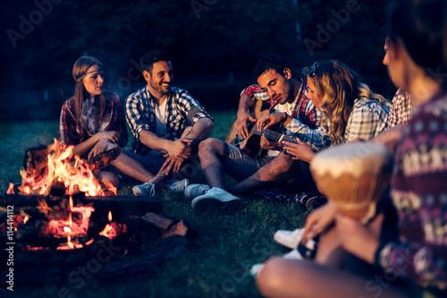 Fotografia Friends enjoying music near campfire