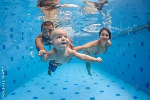 Happy full family - mother, father, baby son learn to swim, dive underwater with fun in pool to keep fit Fototapeta