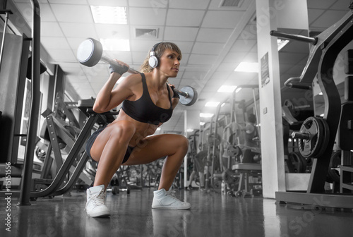 In the gym.fitness model doing squats and white headphones