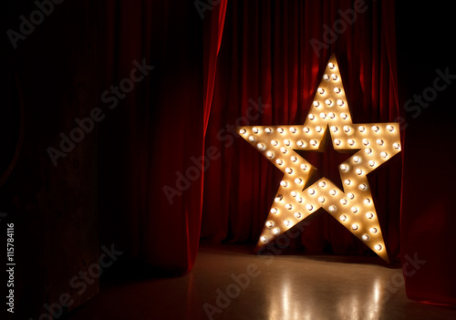 Obraz na płótnie Photo of golden star with light bulbs on red velvet curtain on stage