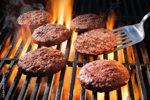 Valokuvatapetti Beef hamburger patties sizzling on the barbecue