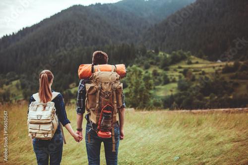 фотография A couple hikers Hiking with backpacks walk along a beautiful mountain area holding hands