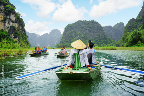 Tourists in boats. Rowers using feet to propel oars, Vietnam