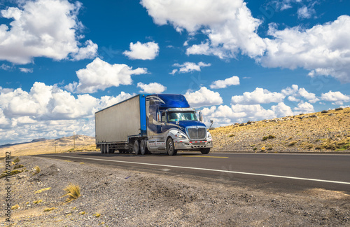 Fototapeta premium Niebieska ciężarówka porusza się na autostradzie