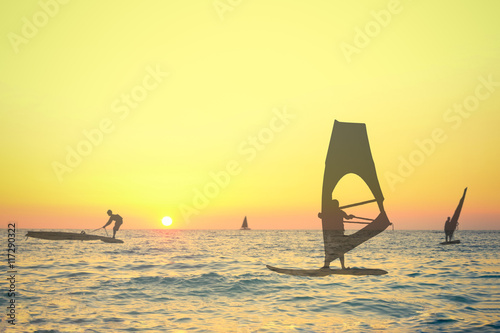 Transparent silhouettes double exposure of wind surfers on sea at the sunset. Sport, summer and vacation concepts.