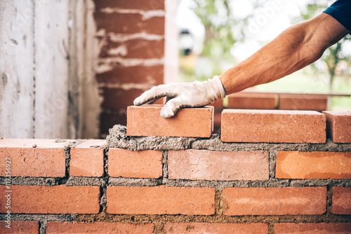 Fotografia industrial bricklayer worker placing bricks on cement while building exterior wa