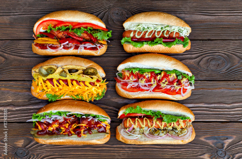 Obraz na plátně A lot of big delicious hot dogs with sauce and vegetables on wooden background