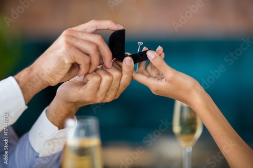 Man proposing to woman offering engagement ring