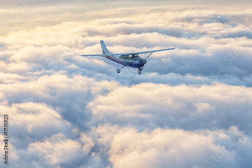 Canvas Print Small single engine airplane flying in the gorgeous sunset sky