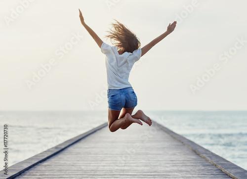 Fototapeta Back view of jumping girl on the pier