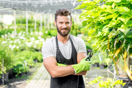 Valokuva Portrait of handsome gardener in black apron and working gloves in the greenhouse