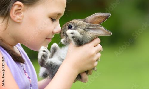 Fotografia Girl is holding a little rabbit