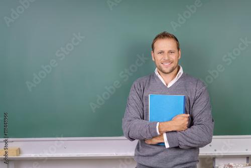 Canvas Print freundlicher lehrer steht mit unterlagen im klassenraum