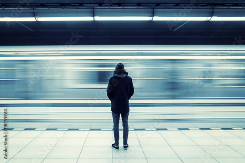 Lonely man shot from behind at subway station with blurry moving train