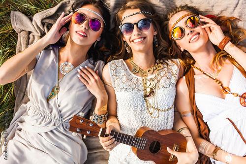 Fototapeta Three cute hippie girl lying on the plaid outdoors, best friends having fun and
