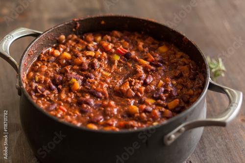 Slika na platnu Organic Vegetarian Chili In Iron Pot Served With Rosemary On Dis