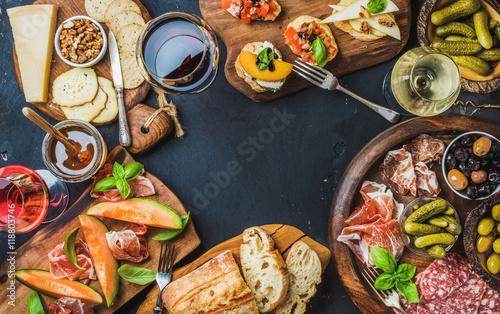 Italian wine antipasti snack variety over dark background, top view, copy space, Fototapeta