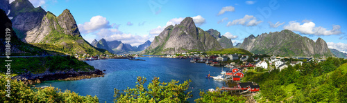 Stampa su Tela Reine in Lofoten Islands, Norway, with traditional red rorbu huts under blue sky with clouds