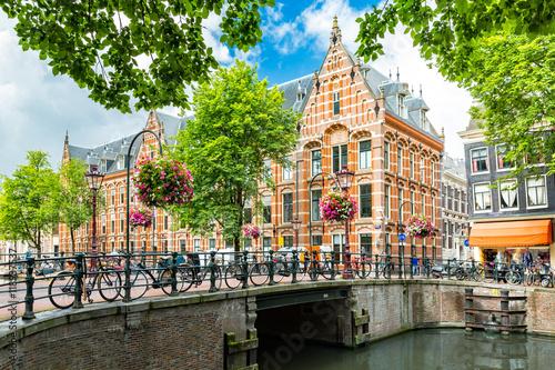 Fototapeta premium Typowy pejzaż miejski Amsterdamu od strony kanału, naprzeciwko XVII-wiecznej siedziby holenderskiej Kompanii Wschodnioindyjskiej, obecnie używany przez Uniwersytet w Amsterdamie