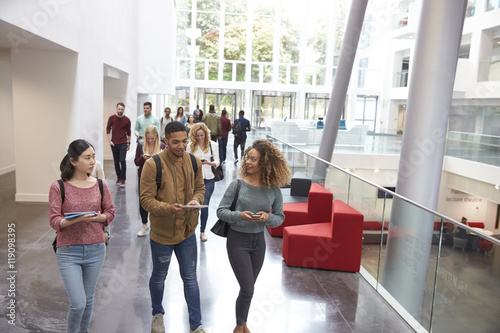 Photo Students walk and talk using mobile devices in university
