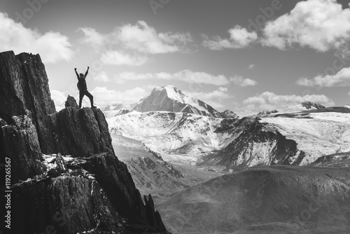 Canvas Print Man stands in winner pose on the cliff. Greyscale