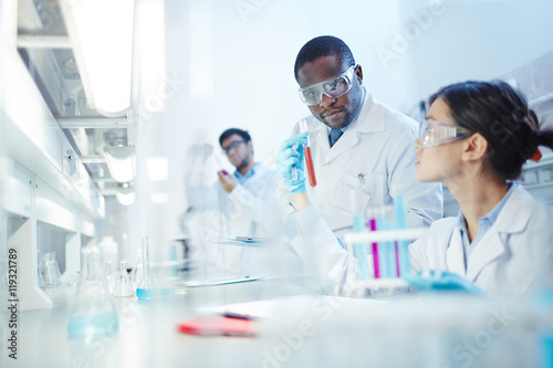 Female Asian laboratory scientist in lab coat and safety goggles showing test tube with red liquid to curious African-American colleague in laboratory. Latin-American scientist in background.