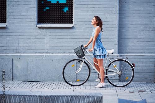 Szczęśliwa kobieta z rower stoi przeciw ceglanemu budynkowi