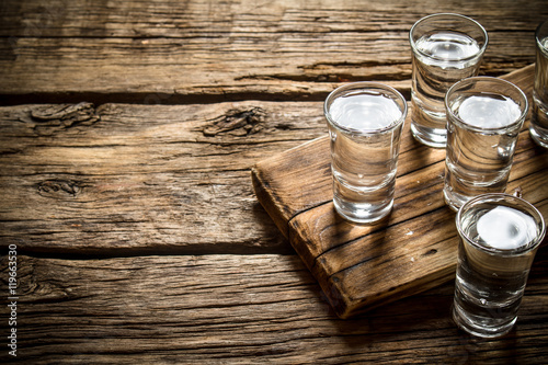 Fotografia Glasses with vodka on the old Board.