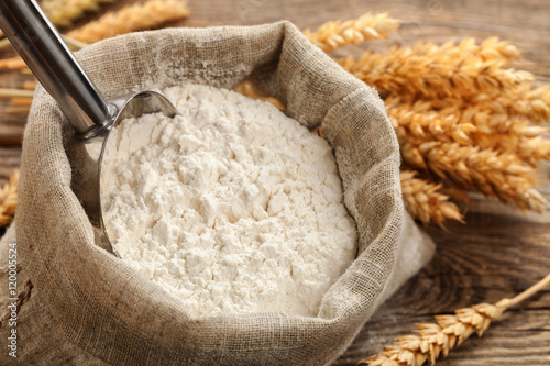 Fotografiet Wheat flour in a bag with wheat spikelets .