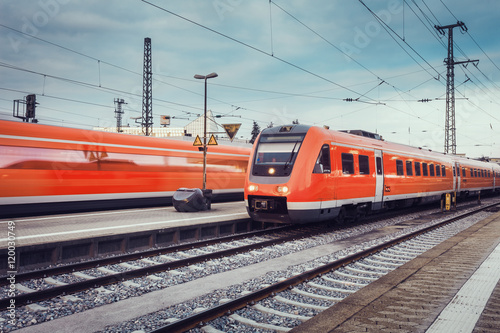 Wallpaper Mural Modern high speed red passenger commuter trains at the railway platform at sunset with vintage toning