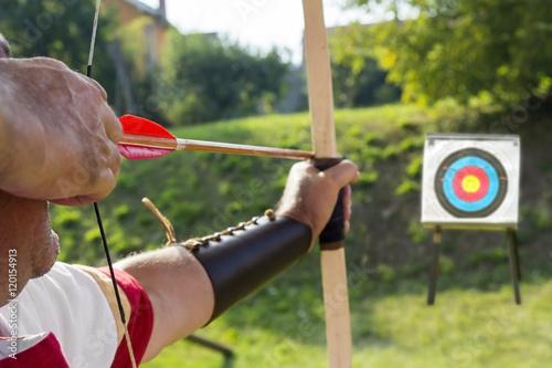 Fototapeta Medieval archer shoot at a target