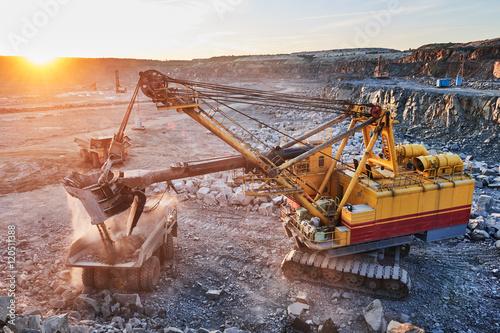 Photo Mining. excavator loading granite or ore into dump truck