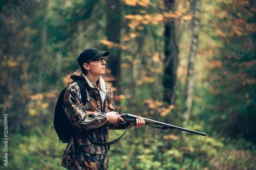 Male hunter in the autumn forest. A man holding a gun. Fototapeta