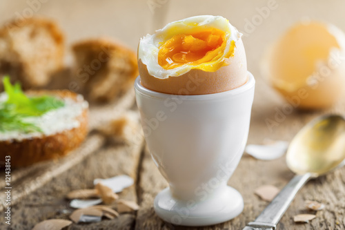Traditional breakfast with perfect soft boiled egg and sandwich with butter and dill. International cuisine food.