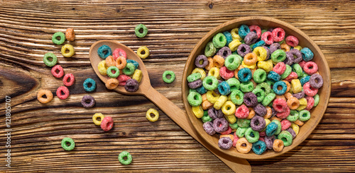 Canvas Print wooden spoon and wooden bowl with colorful cereal